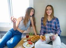 Filles de meilleur ami mangeant de la pizza dans la cuisine Photo stock