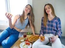 Filles de meilleur ami mangeant de la pizza dans la cuisine Image stock