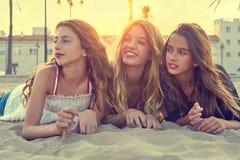 Filles de meilleurs amis au sable de plage de coucher du soleil Photo libre de droits