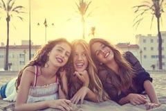 Filles de meilleurs amis au sable de plage de coucher du soleil Photographie stock libre de droits