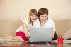 Filles de merveille regardant à l'ordinateur portatif Photographie stock