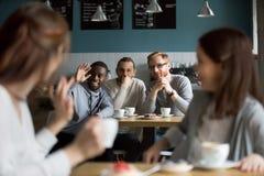 Filles de ondulation de sourire africaines de salutation de main d'homme se réunissant en café Photo stock