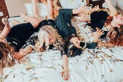 Filles de partie de thème détendant l'excitation de confettis de lit photographie stock libre de droits