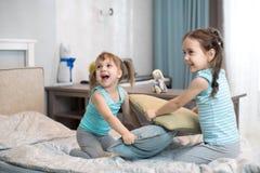 Filles de petits enfants combattant utilisant des oreillers dans la chambre à coucher Photo libre de droits