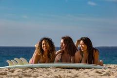 Filles de plage ayant l'amusement avec la planche de surf Images libres de droits