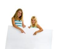 Filles de soeur avec le panneau blanc Photos stock