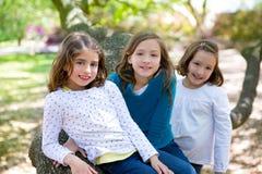 Filles de soeur d'ami se reposant sur la nature de tronc d'arbre Photographie stock