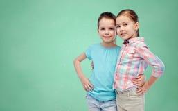 Filles de sourire étreignant au-dessus du conseil pédagogique vert Photo libre de droits