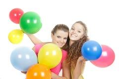 Filles de sourire avec des ballons au-dessus de blanc Image libre de droits