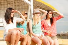 Filles de sourire avec des boissons sur la plage Image stock