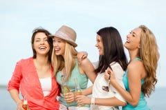 Filles de sourire avec des boissons sur la plage Photographie stock libre de droits