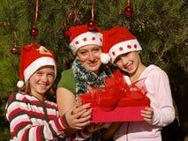 Filles de sourire avec le cadeau de Noël Photographie stock libre de droits