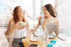 Filles de sourire ayant l'amusement dans le café Image stock