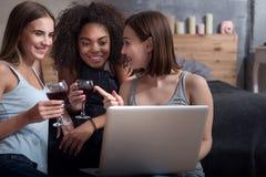 Filles de sourire buvant le vin et à l'aide de l'ordinateur portable Images libres de droits