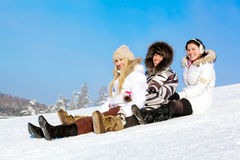 Filles de sourire d'étudiant s'asseyant dans la neige à la pente Photographie stock libre de droits