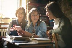 Filles de sourire d'étudiants ayant la conversation et l'utilisation futées Image libre de droits