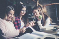 Filles de sourire d'étudiants dans le travail fonctionnant de bibliothèque Images libres de droits