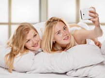 Filles de sourire d'amis faisant le selfie à la maison Image stock