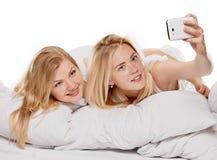 Filles de sourire d'amis faisant le selfie à la maison Photographie stock