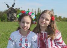 Filles de sourire dans les costumes nationaux dans la campagne avec le vieux moulin à vent derrière Images stock