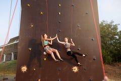Filles de sourire donnant la haute cinq accrochant sur des cordes au mur s'élevant artificiel de formation et assurées par des am Photo stock