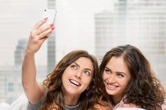 Filles de sourire faisant le selfie à la maison Photos stock