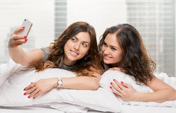 Filles de sourire faisant le selfie à la maison Image libre de droits