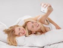 Filles de sourire faisant le selfie à la maison Photographie stock libre de droits