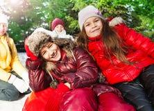 Filles de sourire heureuses s'asseyant sur le glace-bateau rouge Image stock