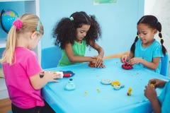 Filles de sourire jouant avec modeler l'argile Photo libre de droits
