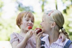 Filles de sourire mangeant des fruits dehors Photos libres de droits