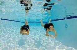 Filles de sourire nageant sous l'eau Images stock