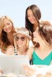 Filles de sourire regardant le PC de comprimé en café Photo libre de droits