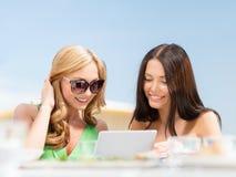 Filles de sourire regardant le PC de comprimé en café Images libres de droits