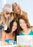 Filles de sourire regardant le PC de comprimé en café Image stock