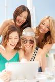 Filles de sourire regardant le PC de comprimé en café Photographie stock libre de droits