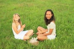 Filles de sourire s'asseyant sur l'herbe Photographie stock