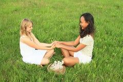 Filles de sourire s'asseyant sur l'herbe Photos libres de droits
