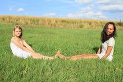 Filles de sourire s'asseyant sur l'herbe Photographie stock libre de droits