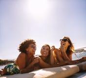 Filles de sourire se trouvant sur la plate-forme de yacht Image stock