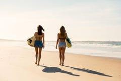 Filles de surfer marchant sur la plage Photos libres de droits