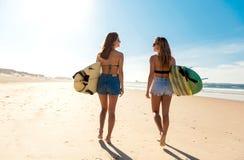 Filles de surfer marchant sur la plage Images stock