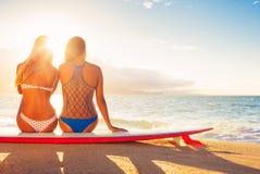 Filles de surfer sur la plage au coucher du soleil Photo stock