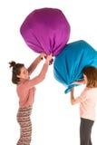 Filles drôles combattant avec des chaises de sac à haricots Image libre de droits