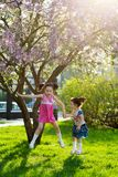 Filles dr?les marchant sur la pelouse avec sa m?re Les soeurs jouent ainsi que la maman Soin maternel Famille heureux photos libres de droits