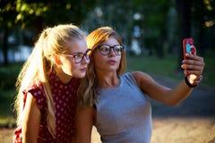 Filles en verres faisant le selfie sur la rue Image stock