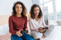 Filles enthousiastes jouant des jeux vidéo ensemble Image stock