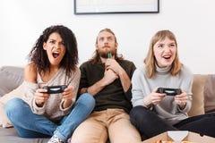Filles enthousiastes jouant des jeux vidéo sur le sofa tandis que garçon près de regarder amazedly là-dessus la bière potable image stock