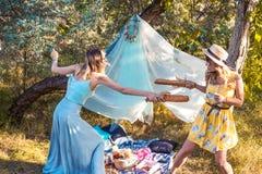 Filles espiègles combattant avec la baguette de pain faisant le pique-nique Photo libre de droits