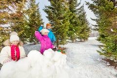 Filles et garçon jouant le combat de jeu de boules de neige Image stock